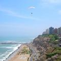 Een parapenter zweeft boven het strand bij Lima